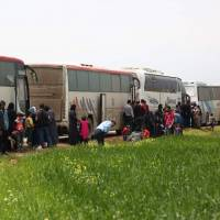Buses carrying Jaish al-Islam fighters and their families from their former rebel bastion of Douma arrive at the Abu al-Zindeen checkpoint controlled by Turkish-backed rebel fighters near the northern Syrian town of al-Bab on Tuesday. | AFP-JIJI