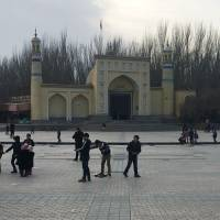 Children play outside the Id-kah mosque in Kashgar, in China's western Xinjiang region, on Feb. 18. The predominantly Uighur area has become one of the most policed places on earth. | AFP-JIJI