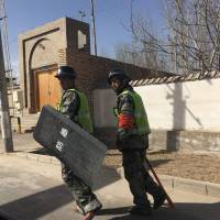 Police patrol a village in Hotan prefecture, in China's western Xinjiang region, on Feb. 17. | AFP-JIJI