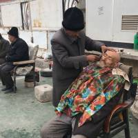 A barber shaves a man outside of the Id-kah mosque in Kashgar, in China's western Xinjiang region, on Feb. 18. | AFP-JIJI