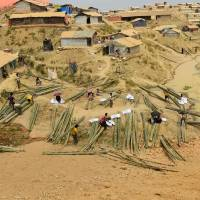 Rohingya refugees rest after collecting bamboo at the Kutupalong refugee camp in Bangladesh's Ukhia district on Thursday. | AFP-JIJI