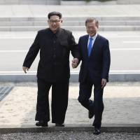 North Korean leader Kim Jong Un and South Korean President Moon Jae-in cross the military demarcation line to the southern side at the border village of Panmunjom in the Demilitarized Zone on Friday. | AP