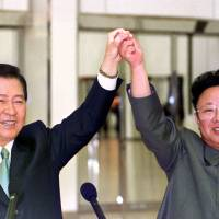 South Korean President Kim Dae-jung and North Korean leader Kim Jong Il join hands before signing an agreement during a historic summit between the two countries in Pyongyang on June 14, 2000. | AFP-JIJI