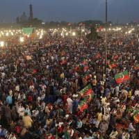 Supporters of opposition leader Imran Khan's party, Tehreek-e-Insaf, attend a rally in Lahore, Pakistan. Tens of thousands of supporters of the popular opposition lawmaker who hopes to become Pakistan's prime minister have gathered in the eastern city of Lahore as his political party launched its campaign for July elections. | AP