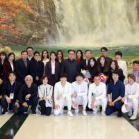 North Korean leader Kim Jong Un poses with South Korean K-pop singers in this photo released Monday. | REUTERS