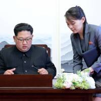 North Korean leader Kim Jong Un prepares to write in a guest book with his sister, Kim Yo Jong, at the Peace House at the truce village of Panmunjom inside the Demilitarized Zone on Friday. | REUTERS