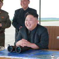 North Korean leader Kim Jong Un watches the launch of a Hwasong-12 missile in this undated photo released in September. | REUTERS