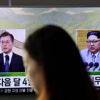 A news program shows file footage of South Korean President Moon Jae-in and North Korean leader Kim Jong Un on a TV screen at the main railway station in Seoul on March 29. | AP