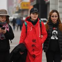 Li Wenzu (center), the wife of detained human rights lawyer Wang Quanzhang, walks with supporters Lin Ermin (right), the wife of rights activist Zhai Yanmin, and Wang Qiaoling, the wife of rights lawyer Li Heping, on the outskirts of Beijing on April 5. | AFP-JIJI