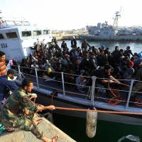 Migrants of different African nationalities arrive at a naval base in Tripoli on Sunday after they were rescued off the coast of Zlitan from two inflatable boats. At least eleven migrants died at sea and another 263 were rescued in two separate operations off the coast of Libya, the country's navy said. | AFP-JIJI