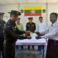 A Myanmar immigration official hands over an identification document to an ethnic Rohingya man, part of a five-member family, at the Taungpyoletwei repatriation camp in Maungdaw, near the Bangladesh border, on Saturday. | AFP-JIJI