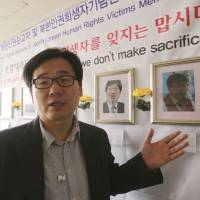 In this April 3 photo, the Rev. Kim Kyou Ho, head of the Seoul-based Chosen People Network, a Christian group that runs a memorial hall in the South Korean capital for the victims, shows a portrait of the Rev. Han Chung-ryeol, right, a Chinese pastor of Korean descent who headed a front-line church in the Chinese border town of Changbai before he was found dead of multiple stab wounds and a punctured skull in April 2016, at his office in Seoul. | AP