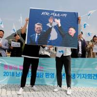 Students hold posters with pictures of South Korean President Moon Jae-in and North Korean leader Kim Jong Un during a pro-unification rally in Seoul on Thursday ahead of the upcoming summit between the North and South. | REUTERS
