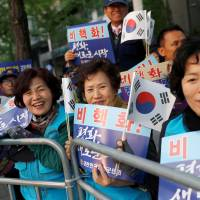Supporters of South Korean President Moon Jae-in hold national flags and signs while waiting for a convoy transporting Moon to leave the Presidential Blue House for the inter-Korean summit, in Seoul, on Friday. | REUTERS