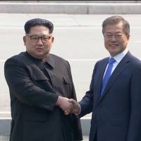 North Korean leader Kim Jong Un shakes hands with South Korean President Moon Jae-in as both of them arrive for the inter-Korean summit Friday at the truce village of Panmunjom, in this still frame taken from video. | REUTERS