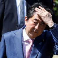 Prime Minister Shinzo Abe speaks to reporters after attending a cherry blossom viewing party at Shinjuku Gyoen in Tokyo on Saturday. | REUTERS