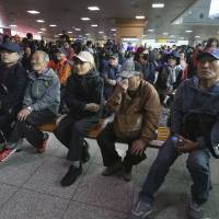 A South Korean man wipes tears as people watch a TV screen at the Seoul Railway Station showing the live broadcast of South Korean President Moon Jae-in meeting with North Korean leader Kim Jong Un on Friday. | AP