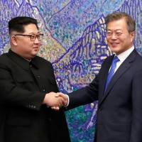 South Korean President Moon Jae-in shakes hands with North Korean leader Kim Jong Un during the inter-Korean summit in the Peace House building on the southern side of the truce village of Panmunjom on Friday. | KOREA SUMMIT PRESS POOL / VIA AFP-JIJI