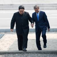 South Korean President Moon Jae-in and North Korean leader Kim Jong Un meet in the truce village of Panmunjom inside the Demilitarized Zone separating the two Koreas on Friday. | KOREA SUMMIT PRESS POOL / VIA REUTERS