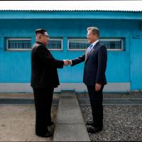 North Korean leader Kim Jong Un shakes hands with South Korean President Moon Jae-in at the Military Demarcation Line that divides their countries ahead of Friday's summit at the truce village of Panmunjom. | AFP-JIJI