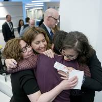 Writers (from left) Alice Crites, Stephanie McCrummen, Amy Gardner and Beth Reinhard embrace in the newsroom after The Washington Post wins two pulitzer prizes Monday in Washington. The Post shared a Pulitzer with the New York Times for their coverage of Russian meddling in the 2016 U.S. presidential election and contacts between President Donald Trump's campaign and Russian officials and won a second Pulitzer for uncovering the decades-old allegations of sexual misconduct against Senate candidate Roy Moore of Alabama. | AP