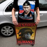 Serbian protester wearing a T-shirt showing Russian President Vladimir Putin holds an anti-NATO poster during a demonstration against Western airstrikes on the Syrian regime, in Belgrade on Sunday. | AFP-JIJI