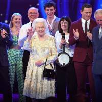 Queen Elizabeth II and her son, Prince Charles (right), join some of the performers on stage during the Queen's Birthday Party concert on the occasion of the monarch's 92nd birthday at the Royal Albert Hall in London on Saturday. | AFP-JIJI
