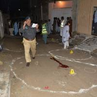 Pakistani investigators collect evidence at the shooting site outside a church in Quetta on Sunday. Two Christians were killed in the drive-by shooting outside a church in southwestern Pakistan, the second such attack on the minority community in the area this month. | AFP-JIJI