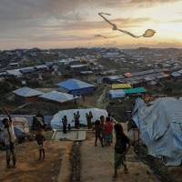 Rohingya refugee children fly improvised kites at the Kutupalong refugee camp near Cox's Bazar, Bangladesh, in December. | REUTERS