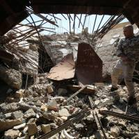 An Iraqi fighter from the Shiite Popular Mobilization Units checks the severely damaged tomb of late Iraqi dictator Saddam Hussein in the village of Al-Awja, on the outskirts of Tikrit, on April 8. | AFP-JIJI