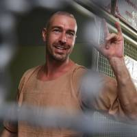 Detained Russian Alexander Kirillov, a self-styled sex guru, gestures as he arrives at a holding cell to face trial at a court in Pattaya on Tuesday. | AFP-JIJI