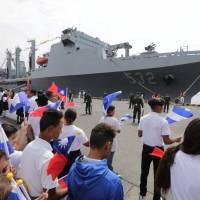Nicaraguan students wave Taiwanese flags to welcome three Taiwanese Navy warships at Corinto port, some 150 km northwest of Managua, on Monday. | AFP-JIJI