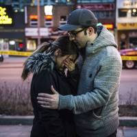 Farzad Salehi consoles his wife, Mehrsa Marjani, who was at a nearby cafe and witnessed the aftermath of a deadly attack that saw a van driver plow down pedestrians on a crowded sidewalk Monday in Toronto. | AP