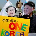 People wear masks of South Korean President Moon Jae-in and North Korean leader Kim Jong Un during a pro-unification rally in Seoul on Wednesday ahead of the upcoming summit between the North and South.