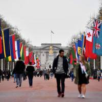 Pedestrians walk underneath flags of Commonwealth countries flying along the Mall that leads to Buckingham Palace in central London on Sunday. | AFP-JIJI