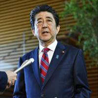 Prime Minister Shinzo Abe speaks to reporters on Sunday at the Prime Minister's Office. | KYODO