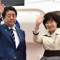 Prime Minister Shinzo Abe and his wife, Akie, wave as they prepare to depart from Tokyo's Haneda airport on Tuesday. | AFP-JIJI