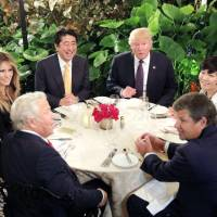 Prime Minister Shinzo Abe and U.S. President Donald Trump attend dinner with their wives at the Mar-a-Lago Club in Palm Beach, Florida, in February 2017. | REUTERS / VIA KYODO