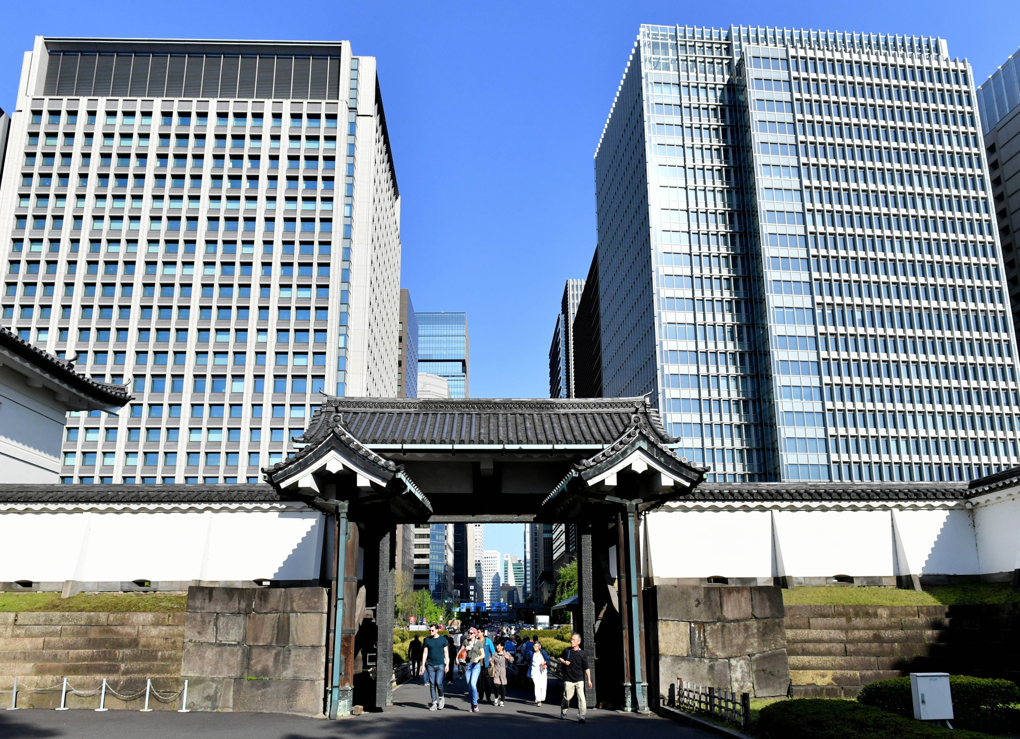 Tourists walk through the Otemon gate of the Imperial Palace against a backdrop of skyscrapers on April 19. | YOSHIAKI MIURA