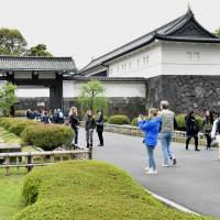 Tourists take photos in front of the Otemon gate at the Imperial Palace in April. | YOSHIAKI MIURA