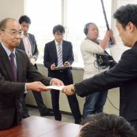 A Mie Prefectural Government official (right) on Thursday hands a license to cultivate cannabis for religious rituals to a member of a local association of Shinto shrines. | KYODO