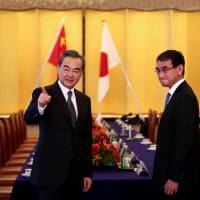 Chinese Foreign Minister Wang Yi gestures as he chats with his Japanese counterpart, Taro Kono, before their meeting in Tokyo on Sunday. | AFP-JIJI