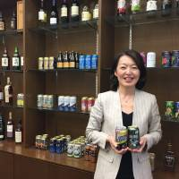 Akiyo Sato, head of Suntory's ready-to-drink alcoholic beverages department, poses with her company's canned chūhai products at Suntory's Tokyo headquarters on April 13. | ALEX MARTIN