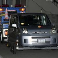 A stolen car believed to have been used by escaped prisoner Tatsuma Hirao sits on a trailer Monday at a police station in Imabari, Ehime Prefecture. | KYODO