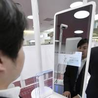 A model tries an unmanned immigration gate equipped with facial recognition technology at Haneda airport in Tokyo last October. | KYODO