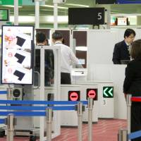 Gates equipped with facial recognition systems are seen at Haneda airport in Tokyo last October.   KYODO