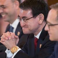Foreign Minister Taro Kono smiles between Italian Foreign Minister Angelino Alfano (left) and German Foreign Minister Heiko Mass (right) during opening remarks at the G7 Foreign Ministers meeting in Toronto on Sunday. | AFP-JIJI
