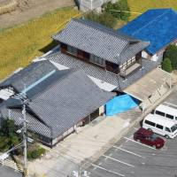 A man was arrested Friday for allegedly killing a 17-year-old girl in 2004 at her home in Hatsukaichi, Hiroshima Prefecture, seen at the center of the photo taken on Oct. 6, 2004, a day after the slaying. | KYODO