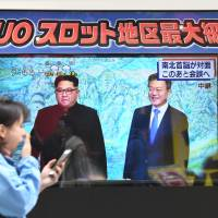 A woman appears to yawn as she walks by a TV in Tokyo on Friday showing South Korean President Moon Jae-in meeting North Korean leader Kim Jong Un. | AFP-JIJI