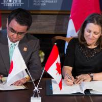 Foreign Minister Taro Kono (left) and his Canadian counterpart Chrystia Freeland sign a mutual defense supply agreement in Toronto on Saturday. The agreement will allow the sharing of military equipment during operations and exercises in Canada, Japan and other locations. | AFP-JIJI